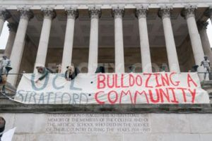 "Protesters against the proposed UCL campus in Stratford occupy the Portico with a banner reading ""UCL Stratford: bulldozing a community""."