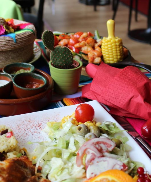 Dining table with platters of Mexican food