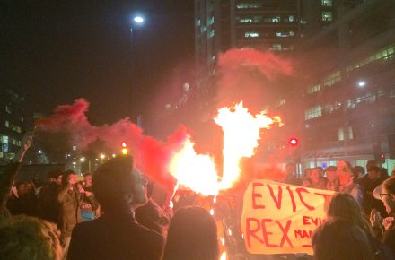 Student protestors carry a burning effigy of Rex Knight around UCL's Bloomsbury campus. There are red flares and a banner calling to evict Rex.