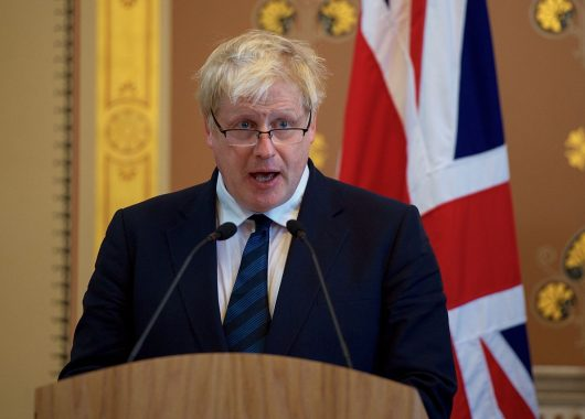 Boris Johnson, Foreign Secretary, speaks from behind a podium, in front of a Union flag, at a press conference in 2017