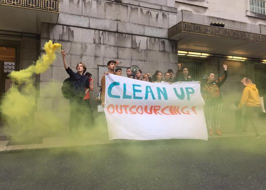 Student activists stand outside Senate House, holding a banner which says 'Clean Up Outsourcing!'